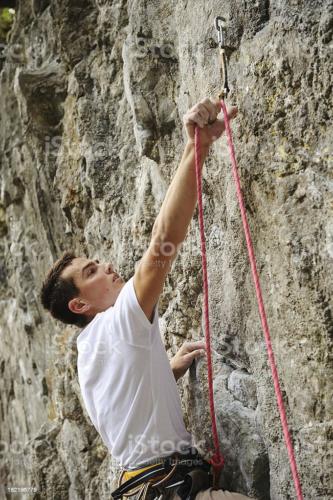 Climber positioning the rope stock photo