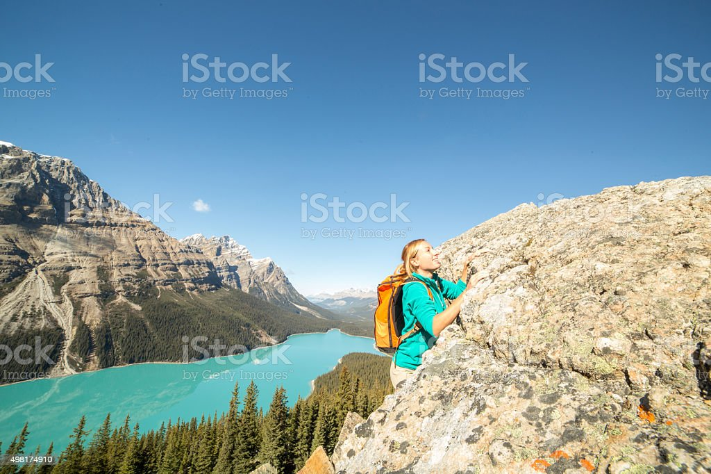 Climber reaching mountain top stock photo