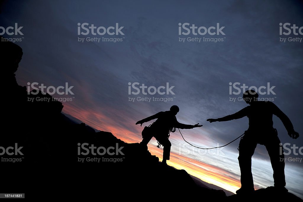 Climber reaching out to partner stock photo