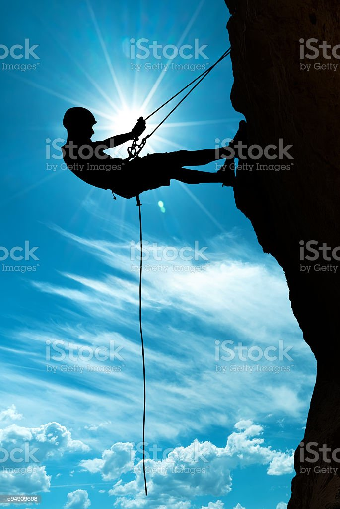 Climber silhouette over shining sun stock photo