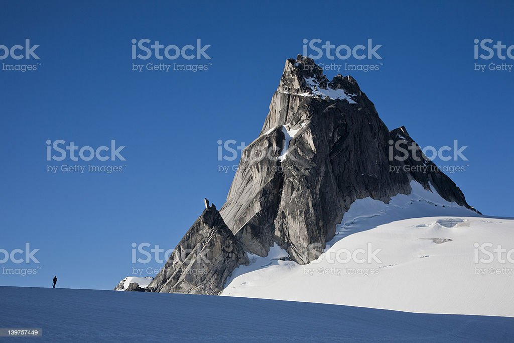 Climber stands below mountain. royalty-free stock photo