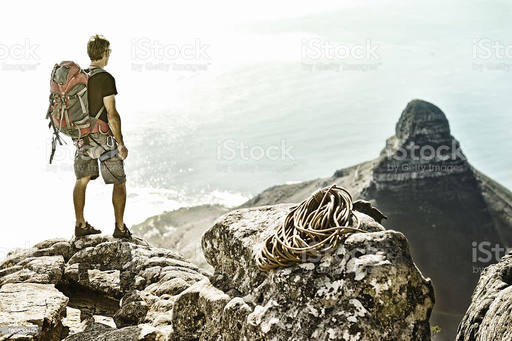 Climber with backpack on mountain summit royalty-free stock photo