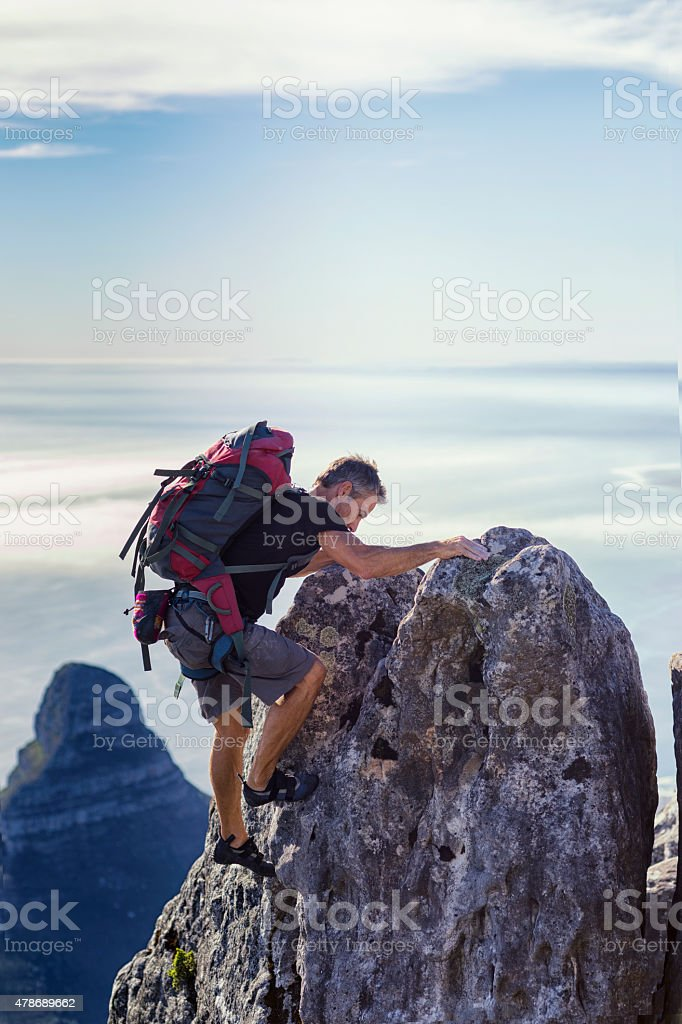 Climber with backpack reaches top of rock stock photo