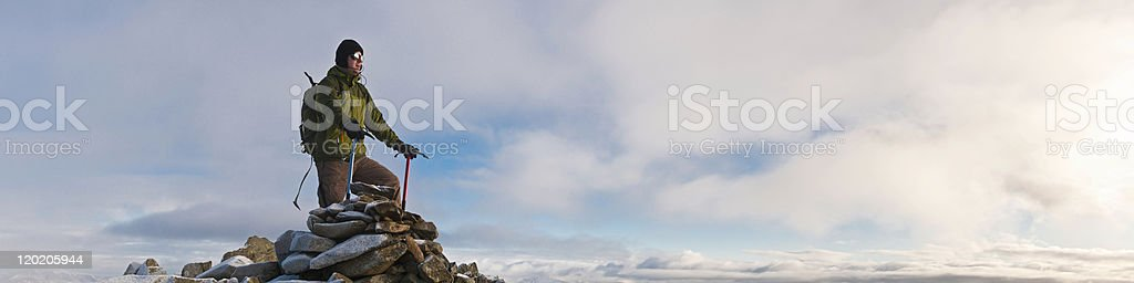 Climber with ice axes on mountain summit looking over clouds royalty-free stock photo