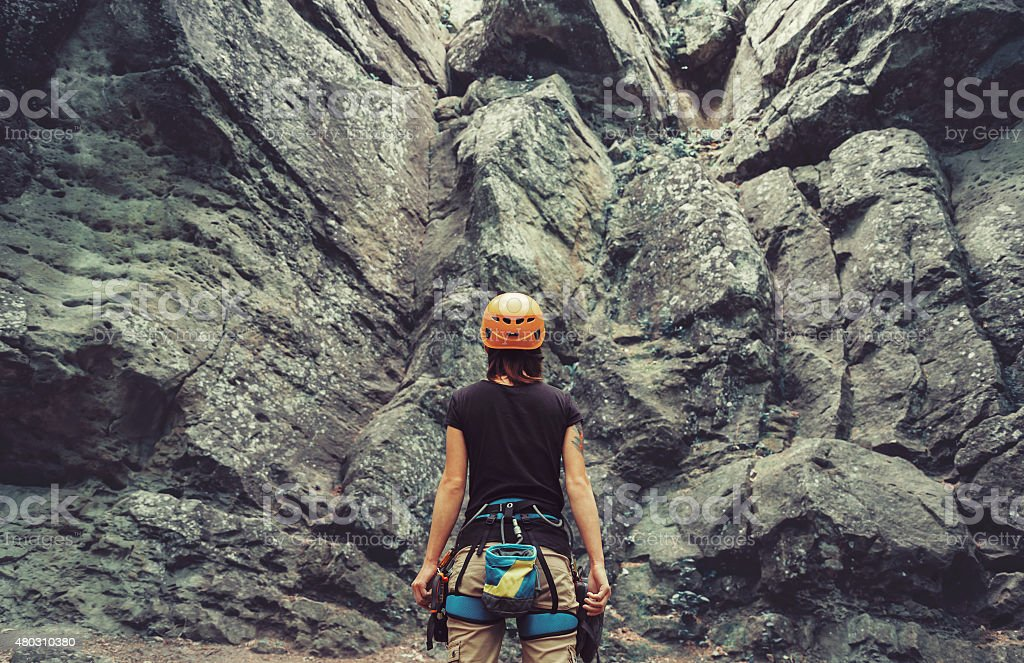 Climber woman standing in front of a stone rock outdoor stock photo