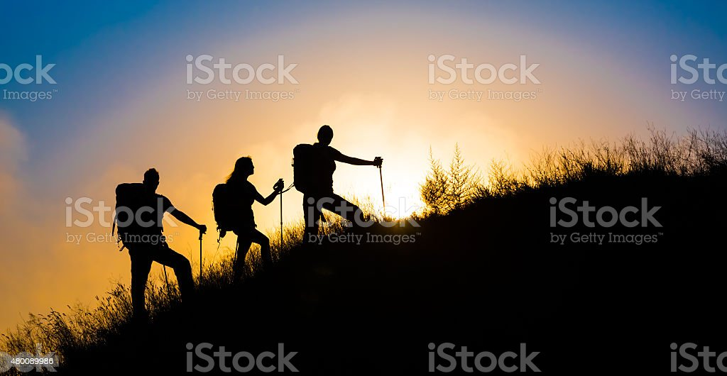 Climbers ascending grassy hill sunset background stock photo