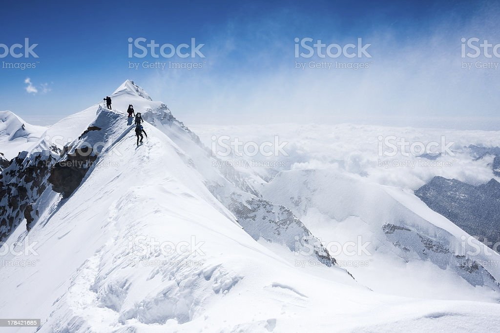 Climbers balancing in blizzard on a narrow mountain ridge stock photo
