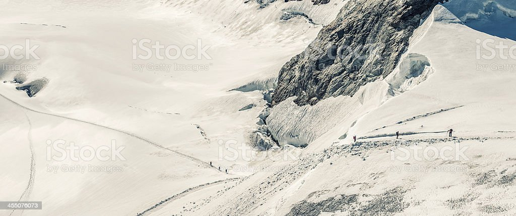 Climbers climbing on Aletsch glacier below Jungfrau summit royalty-free stock photo