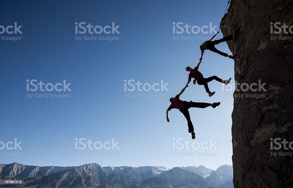 Climbers nearly falling off cliff stock photo