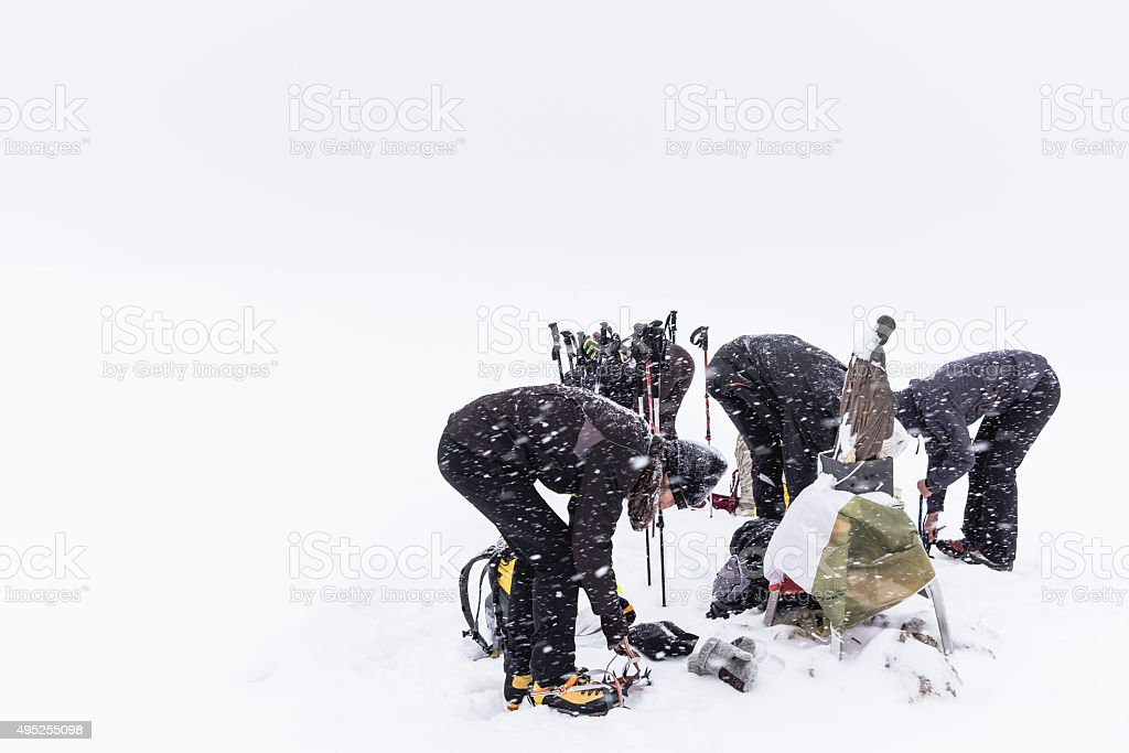 Climbers put crampons on boots stock photo