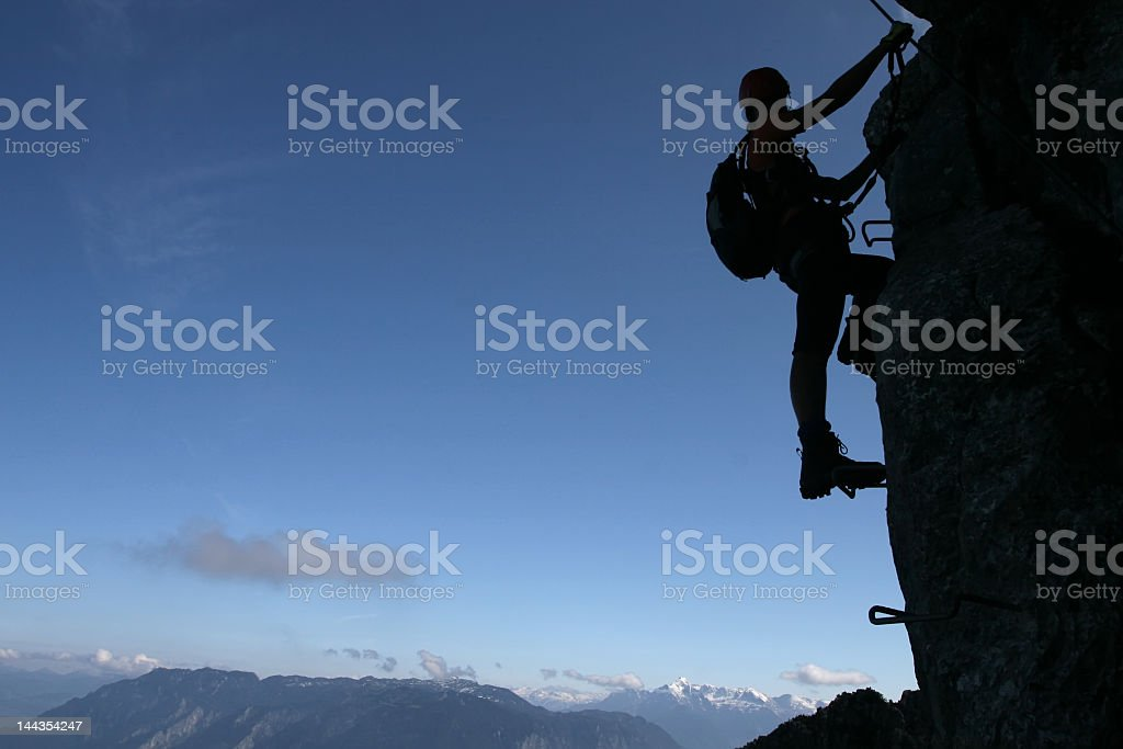 A climbers silhouette against a blue sky and mountains stock photo