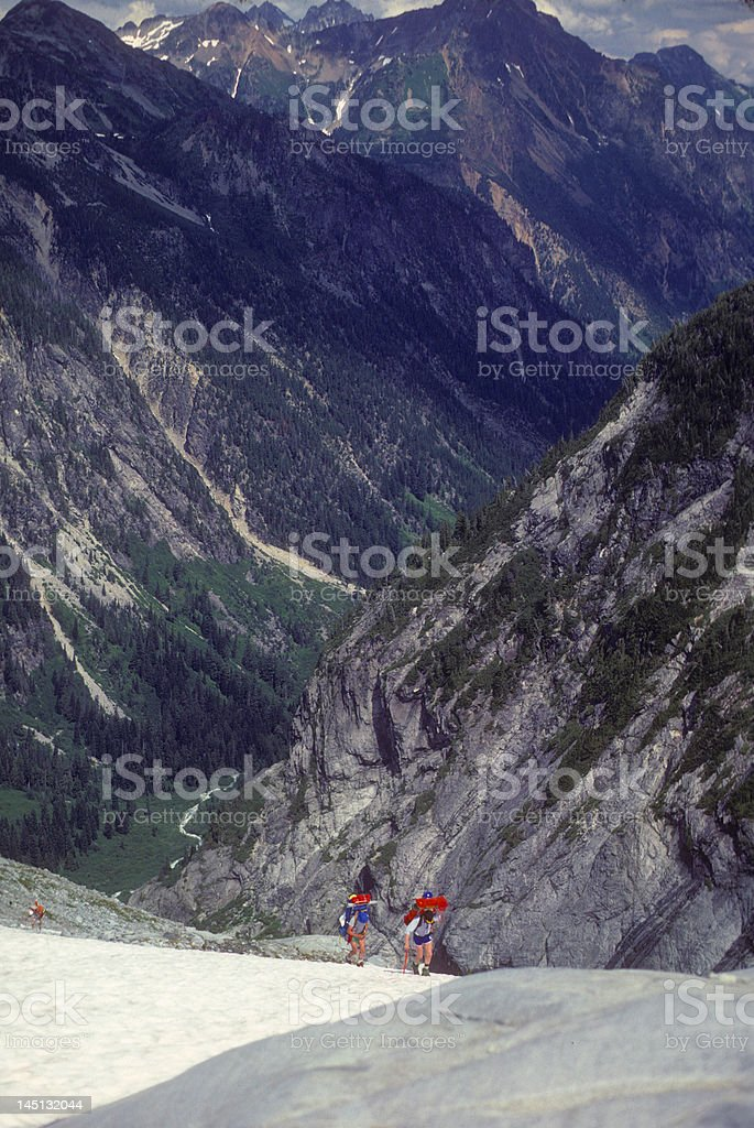 Climbers with full packs descending glacier stock photo