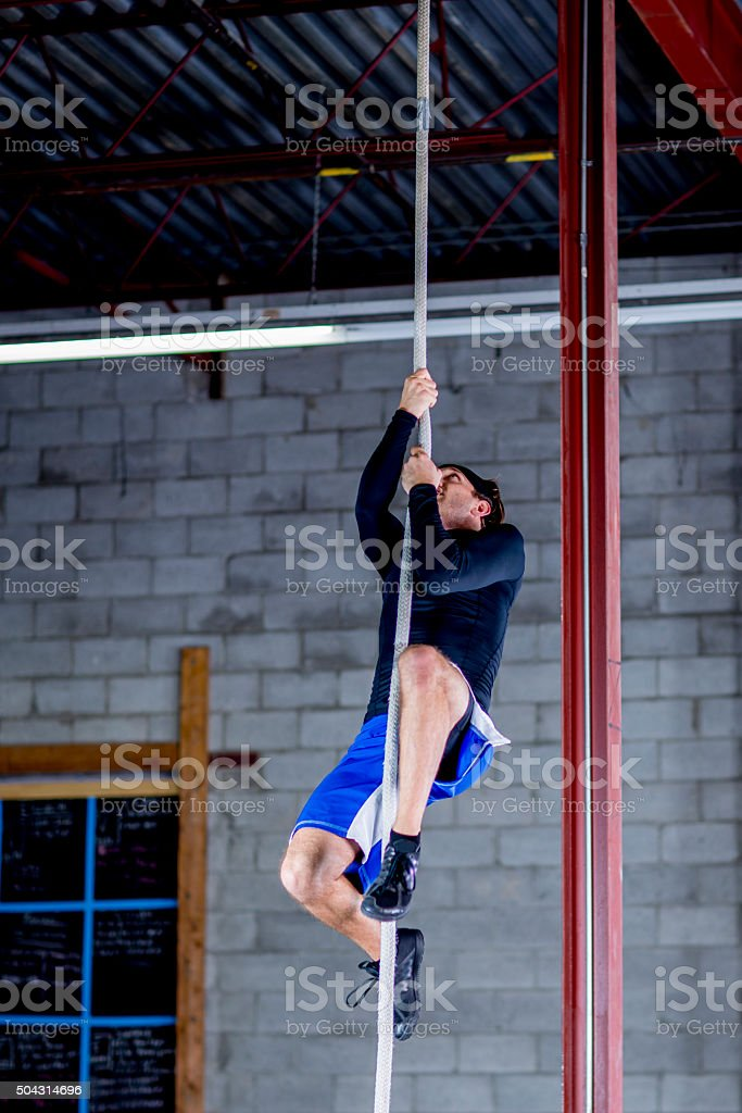 Climbing a Rope in the Gym stock photo