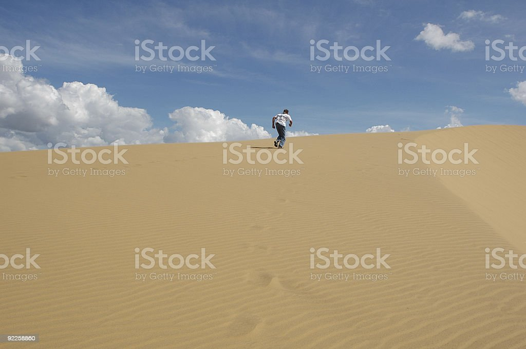 Climbing a sand dune royalty-free stock photo