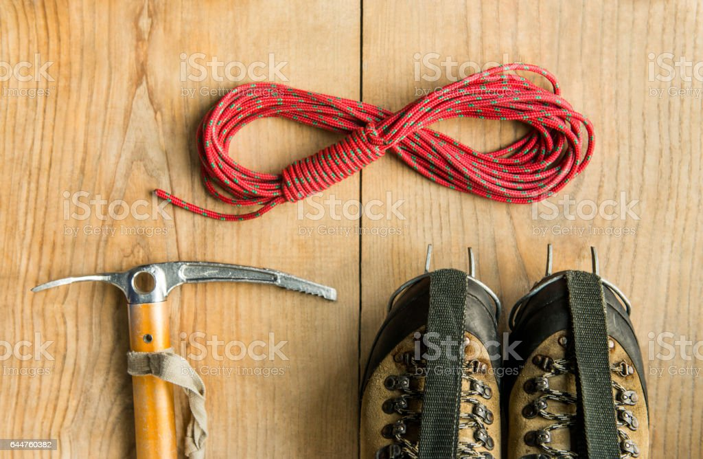 climbing equipment: rope, trekking shoes, ice tools, ice ax, crampons on wooden background stock photo