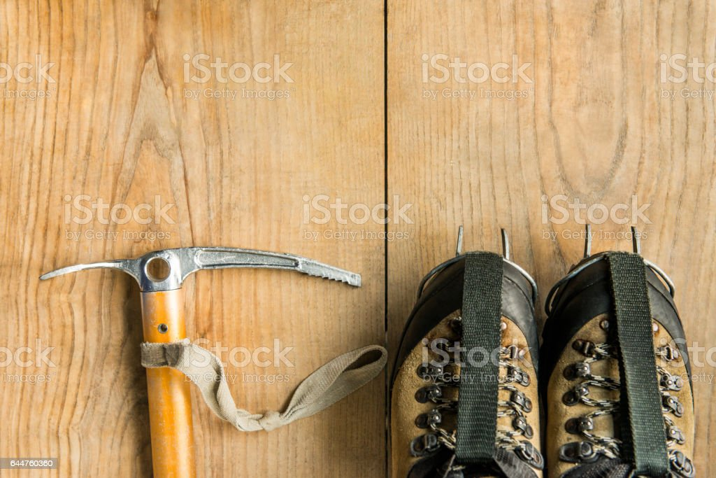 climbing equipment: trekking shoes, ice tools, ice ax, crampons, on wooden background stock photo