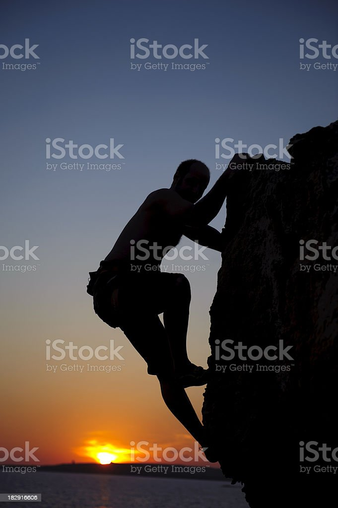Climbing man at sunset stock photo