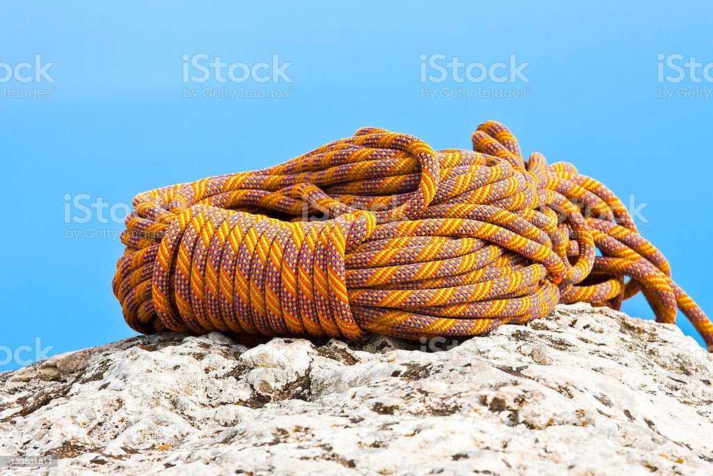 Climbing Rope coiled up and placed on the rock stock photo
