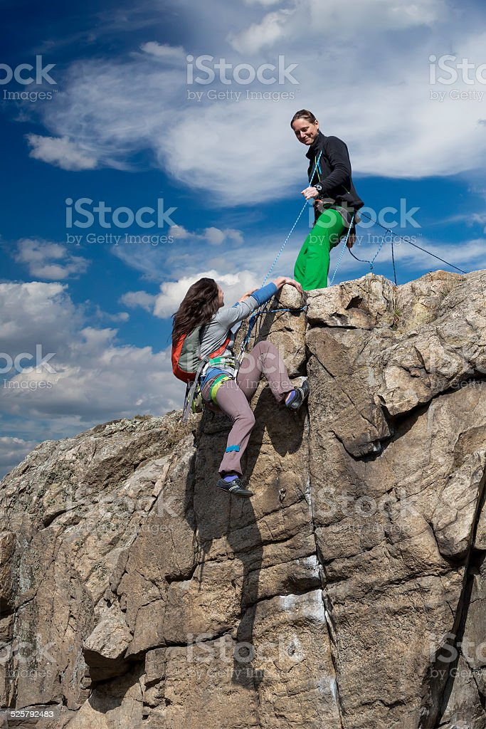Climber helps her partner to rich the summit. Two female climbers,...