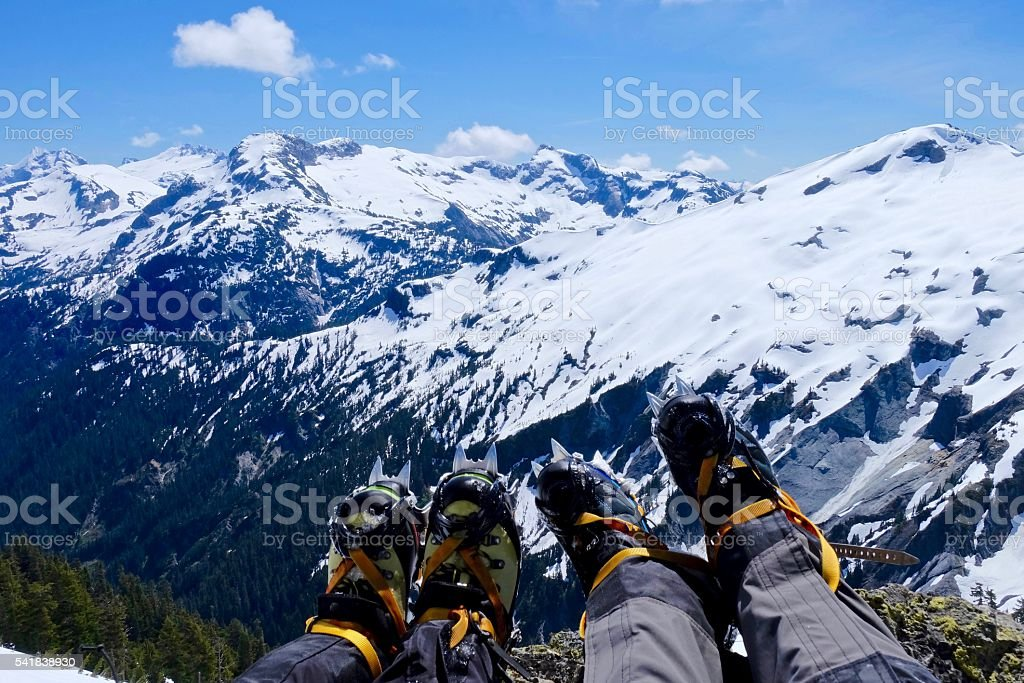 Climers' legs with boots and crampones against snow covered mountains. stock photo