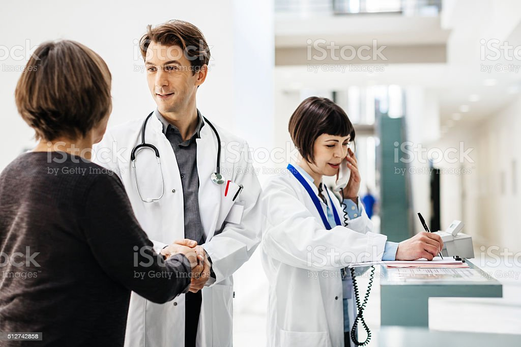 Clinic Staff Welcomes Senior Female Patient stock photo