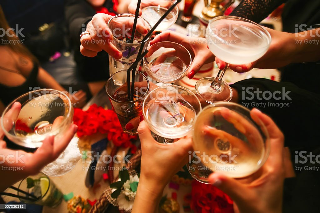 Clinking glasses with alcohol and toasting stock photo