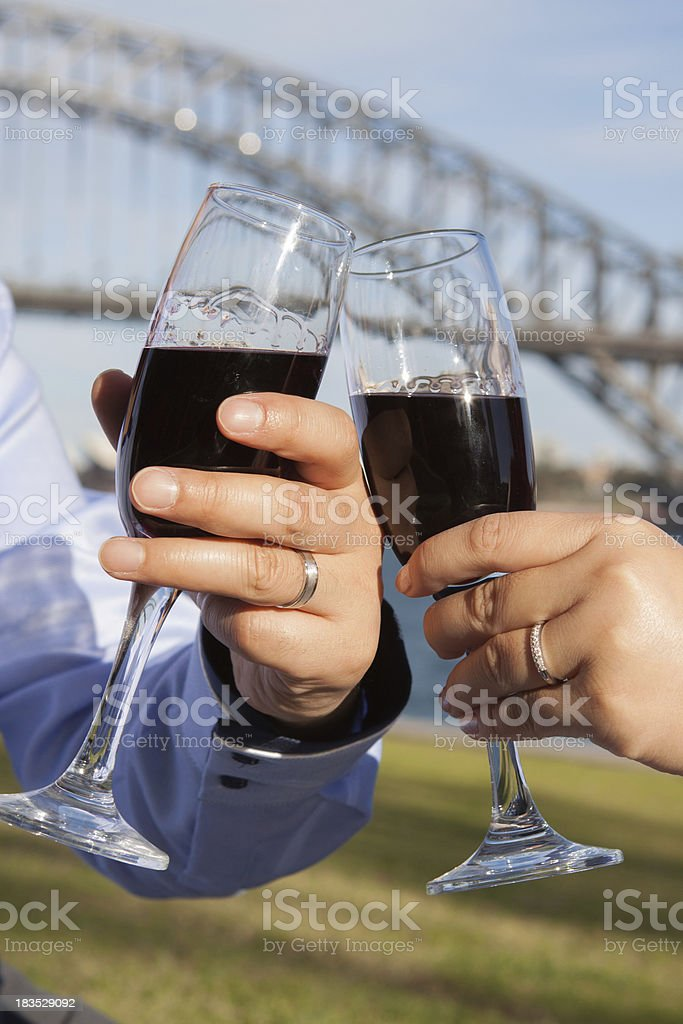 Clinking wine glasses with wedding rings on Sydney Harbour Bridge royalty-free stock photo