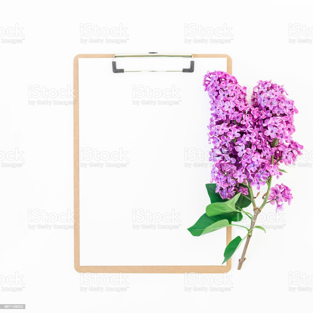 Clipboard and lilac on pink background. Flat lay, top view. Freelancer or blogger concept. stock photo
