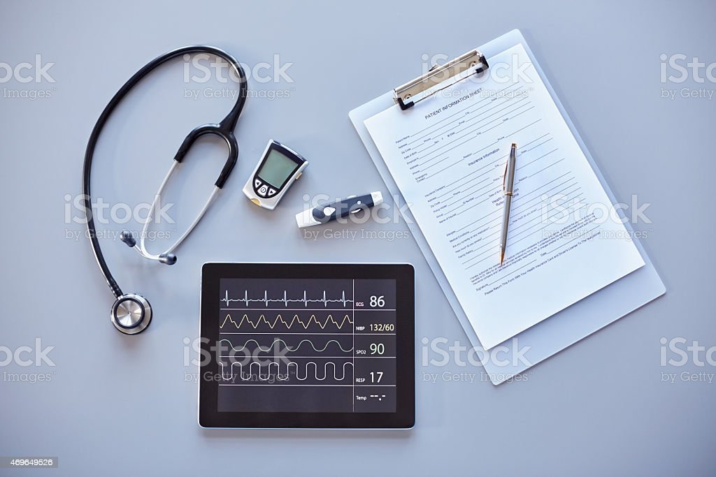 Clipboard, stethoscope, glucometer and digital tablet on desk stock photo