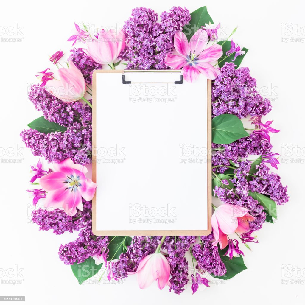 Clipboard, tulips and lilac branch on pink background. Flat lay, top view. Beauty blog concept. stock photo