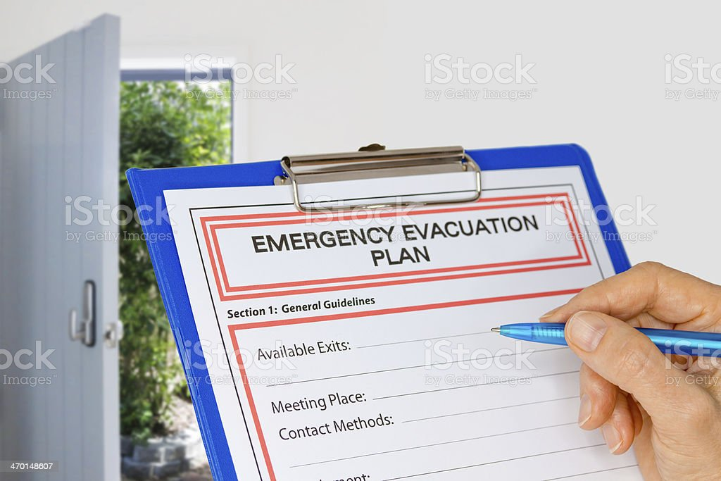 Clipboard with Emergency Evacuation Plan beside Exit Door stock photo