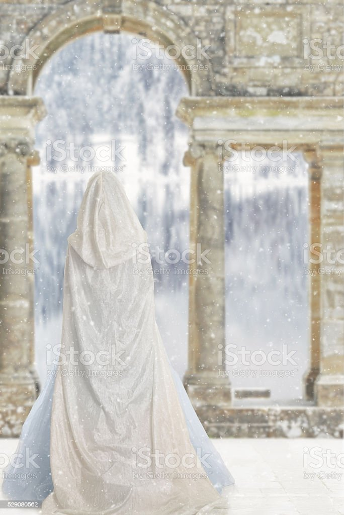 cloaked woman by castle lake stock photo