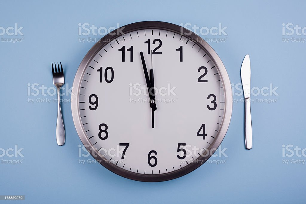 Clock acting as a plate to represent lunch time stock photo