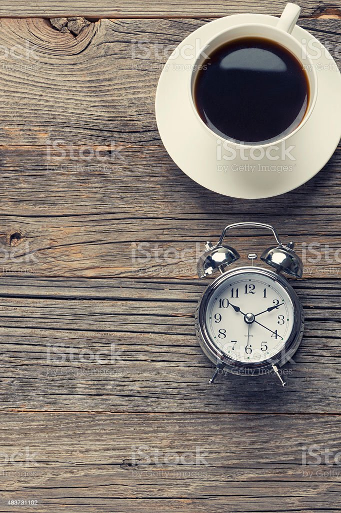 Clock and coffee on a wooden table. stock photo
