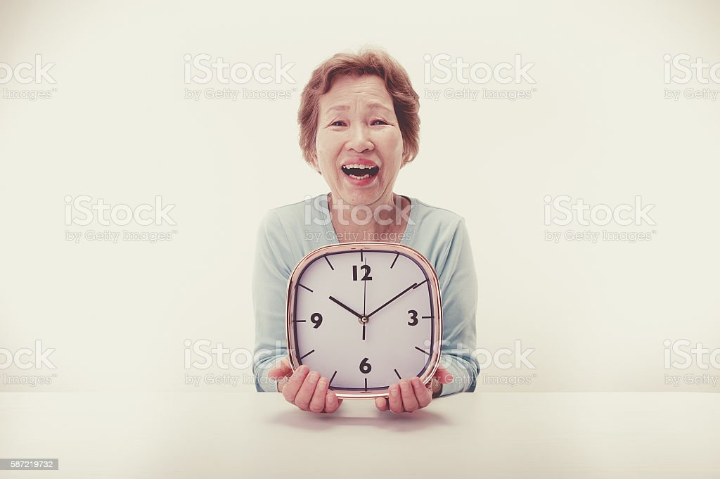 Clock and elderly women stock photo