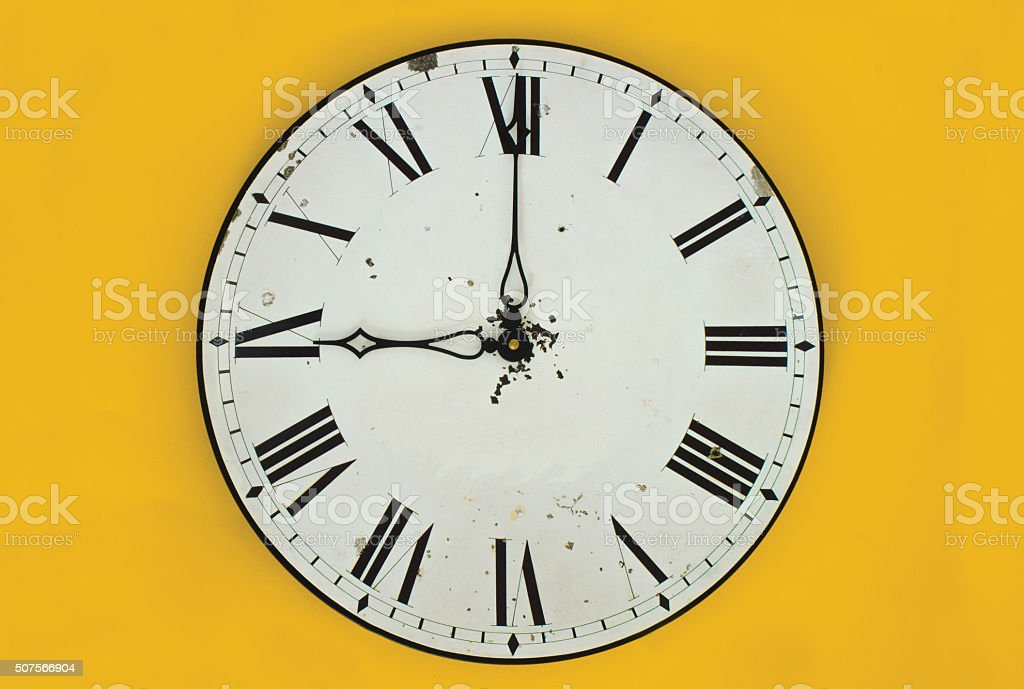 Clock at 9 o'clock in front of plain colourful background stock photo