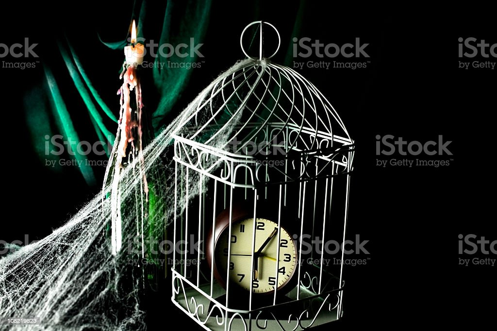 Clock in birdcage, candle bottle spider web stock photo