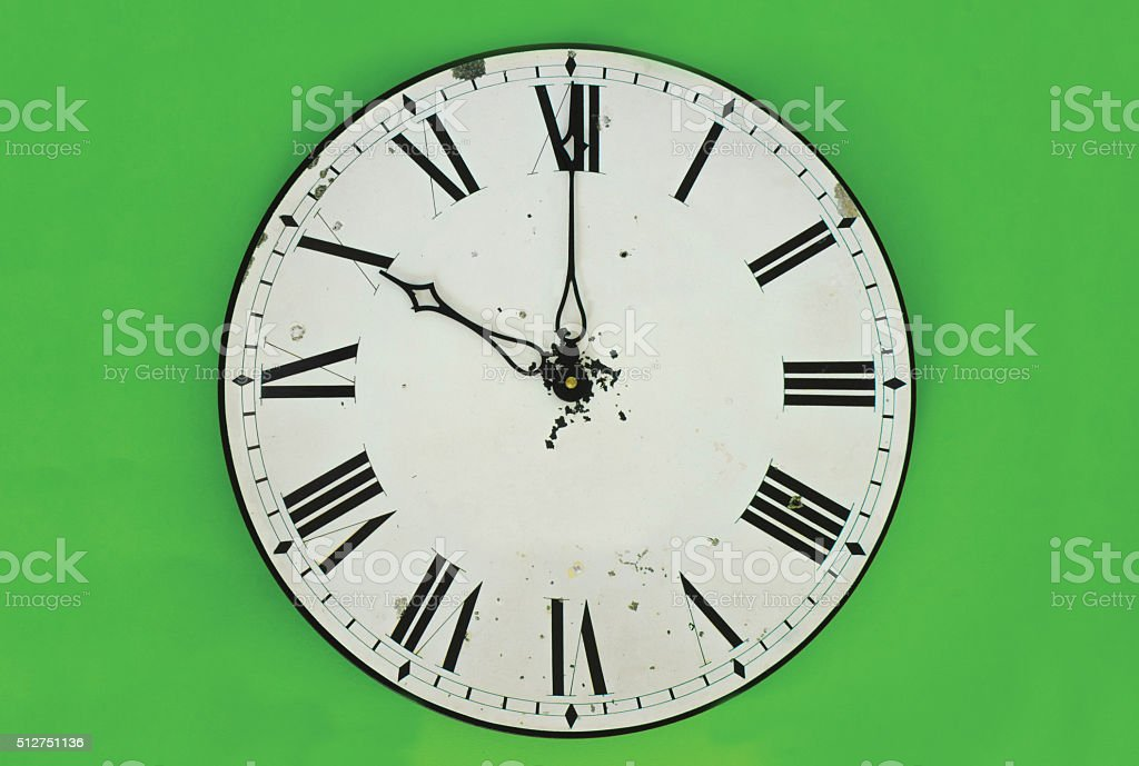 Clock in front of green background stock photo