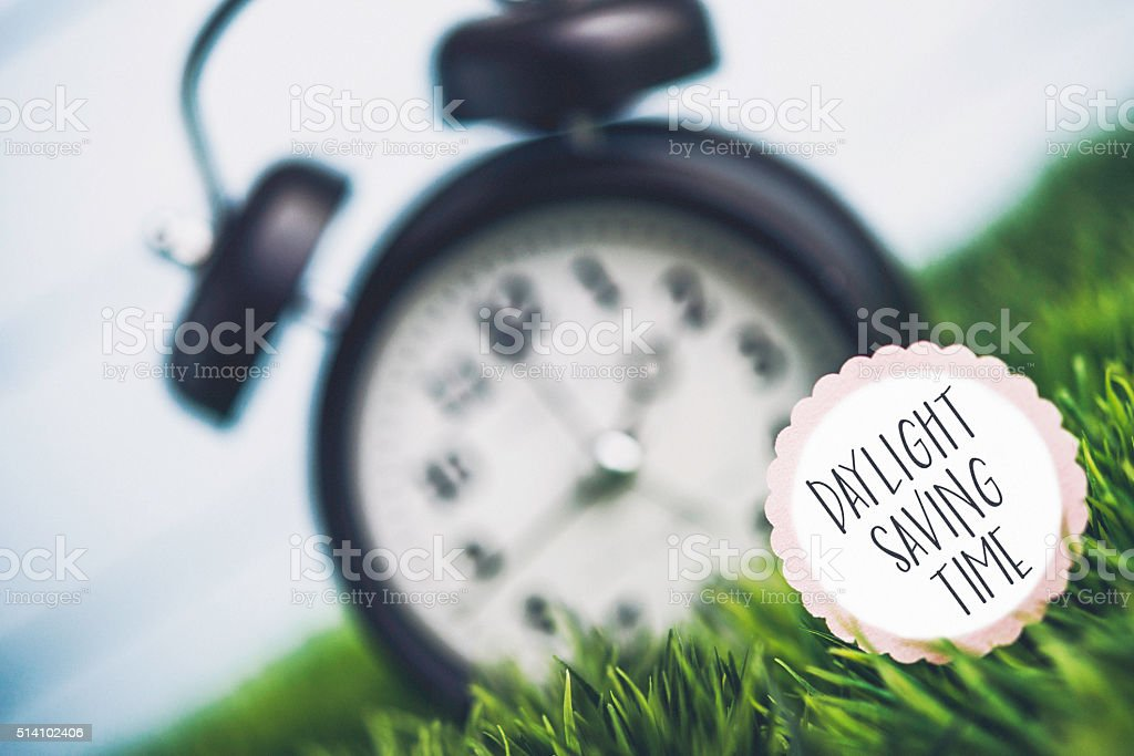 Clock in grass with reminder for Daylight Savings Time stock photo
