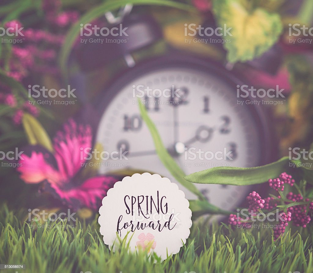 Clock in grass with spring foliage. Daylight Savings Time reminder stock photo