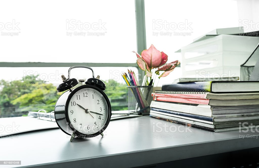 Clock on desk office with stationary in sunlight morning stock photo