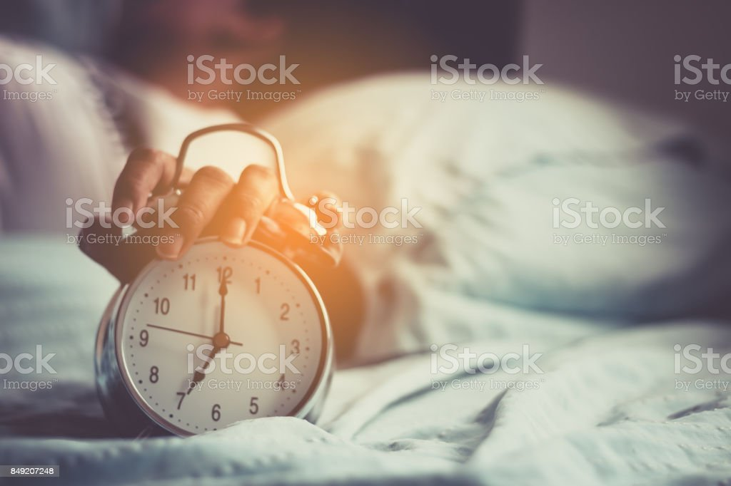 Clock on the bed in the morning. stock photo