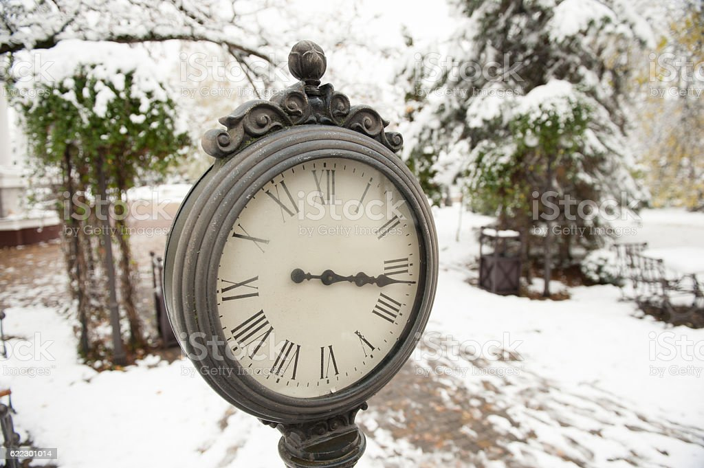 clock on the snowy background stock photo