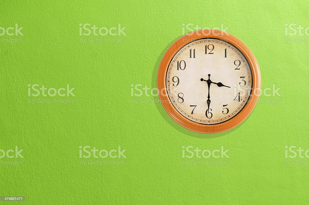 Clock showing 03:30 on a green wall stock photo