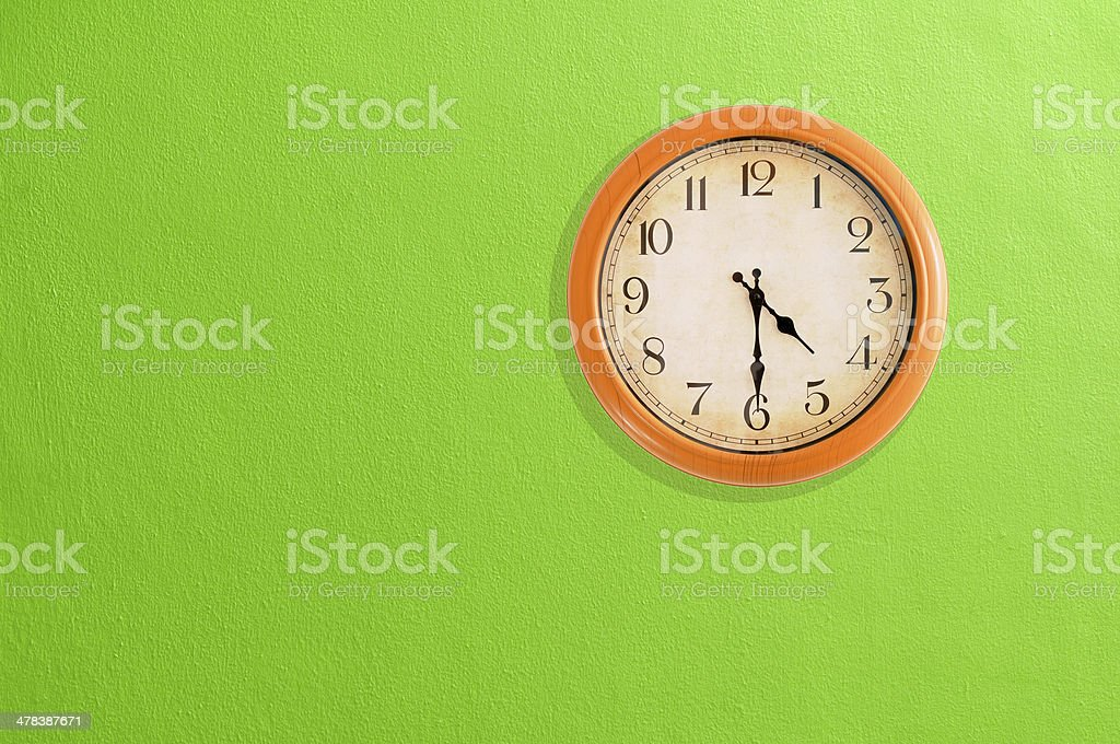 Clock showing 04:30 on a green wall stock photo