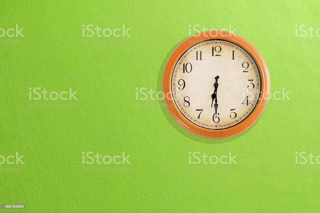 Clock showing 06:30 on a green wall stock photo