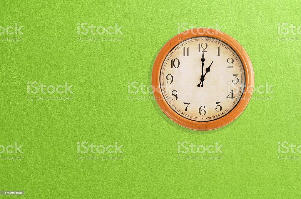 Clock showing 1 o'clock on a green wall royalty-free stock photo