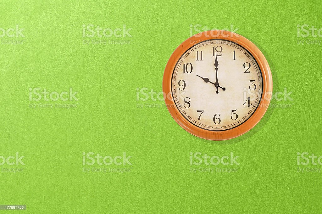 Clock showing 10 o'clock on a green wall stock photo