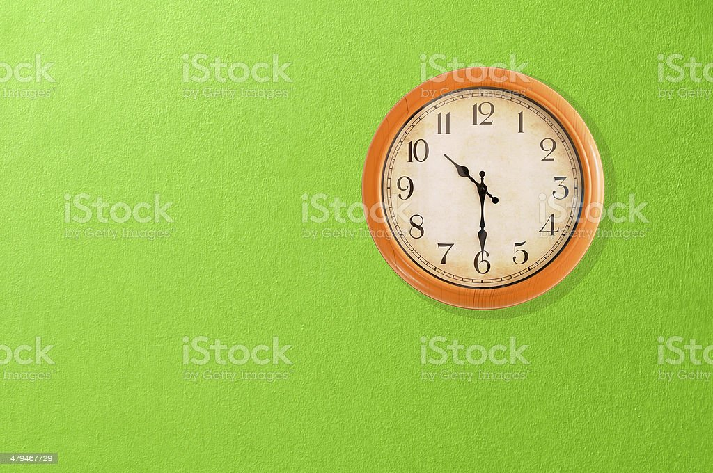Clock showing 10:30 o'clock on a green wall stock photo