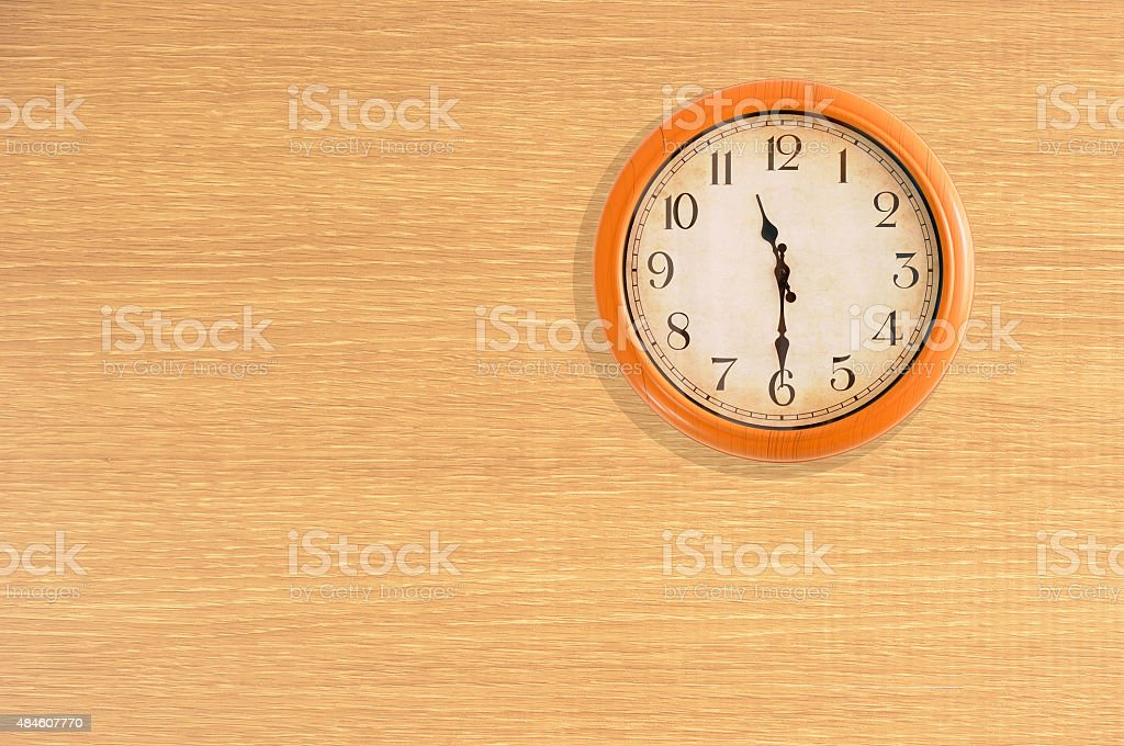 Clock showing 11:30 o'clock on a wooden wall stock photo